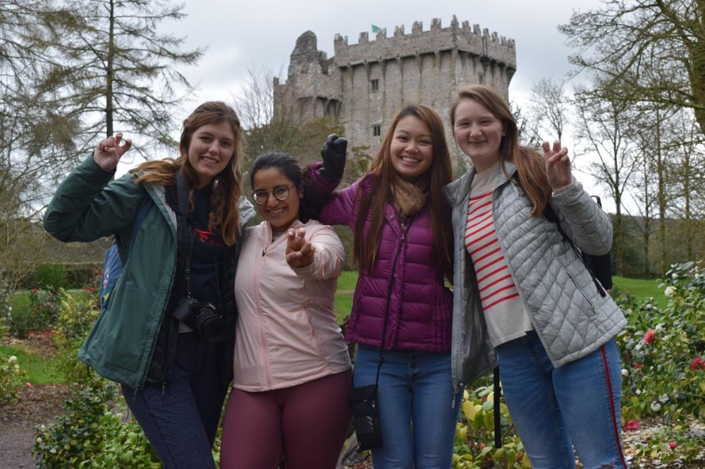 Students smile in front of a castle in Ireland
