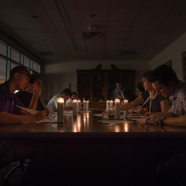 Students write with ink by candlelight