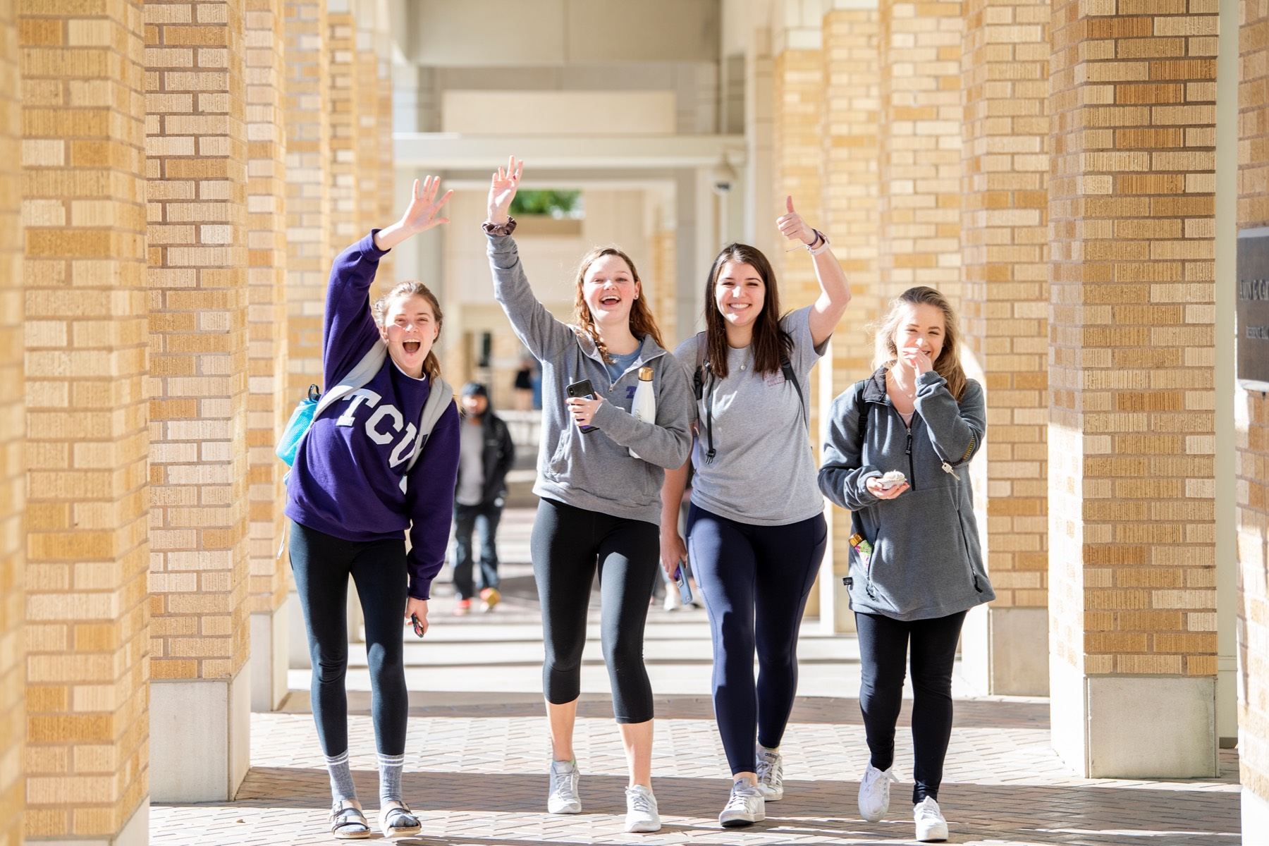 Students wave at the camera