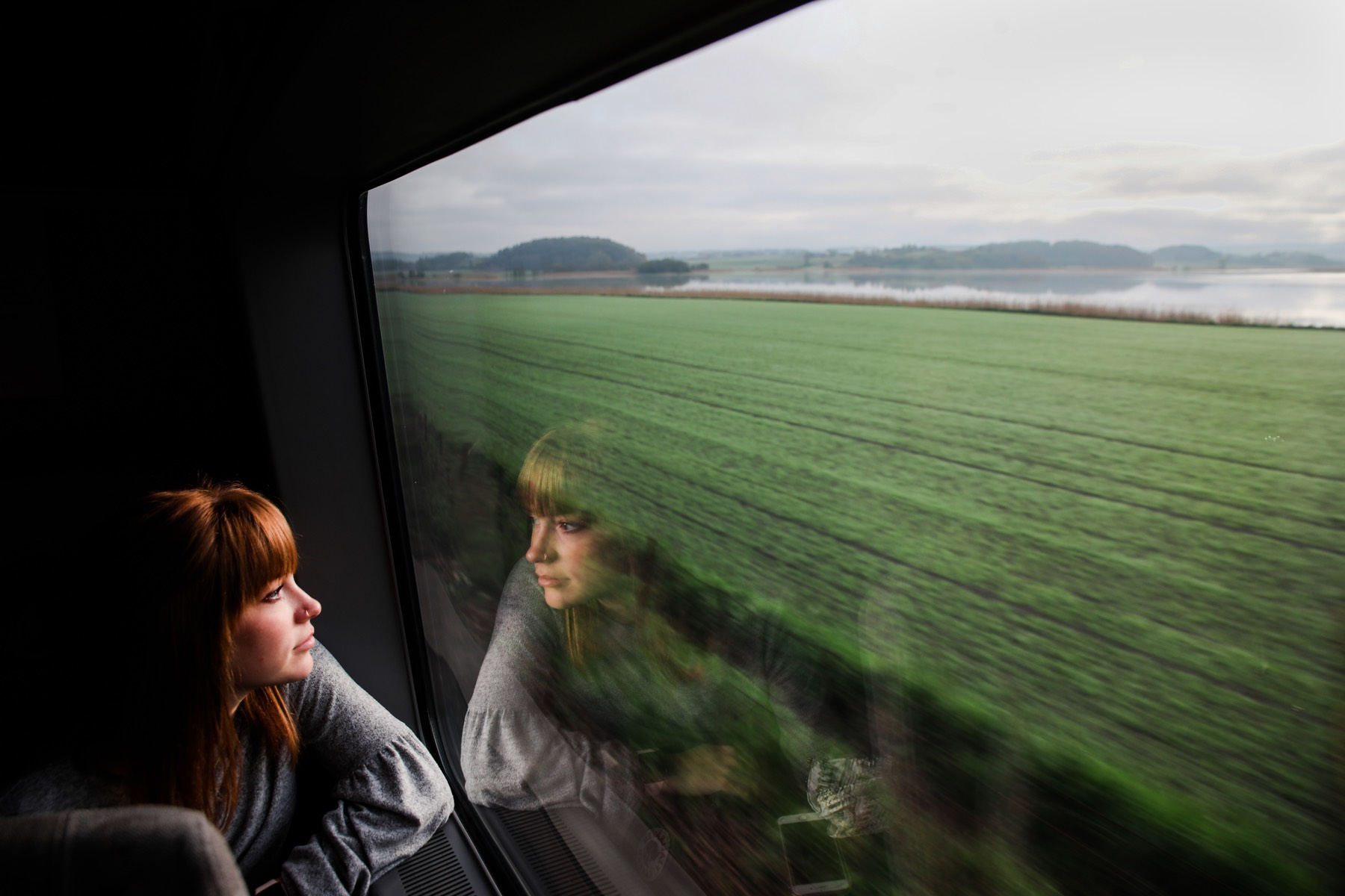 A student looks out a train window