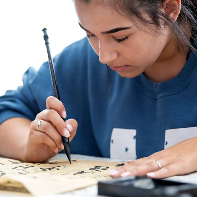 A student practices Chinese calligraphy