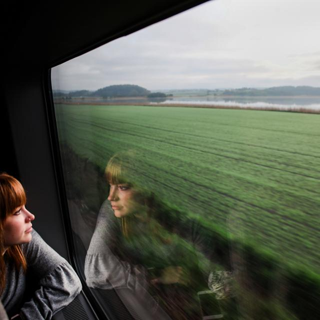 A girl looks out a train window